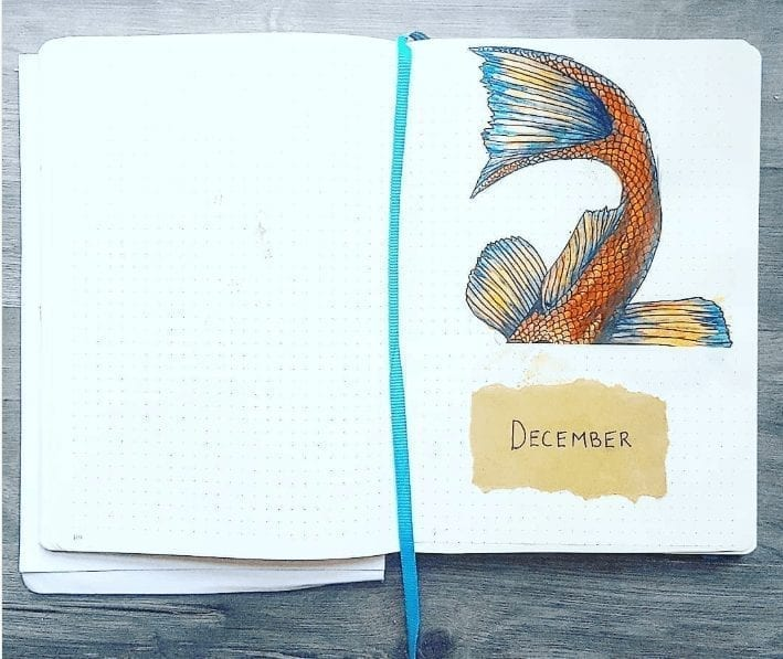 """fishtail art with """"december"""" on brown paper below tail"""