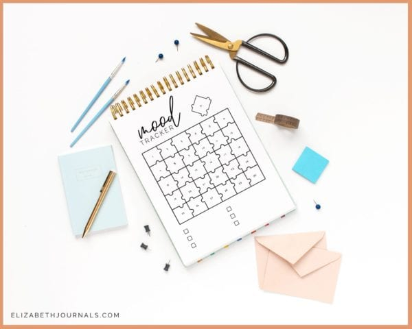 spiral notebook showing 31 page puzzle mood tracker on white surface with pastel blue and pink stationery