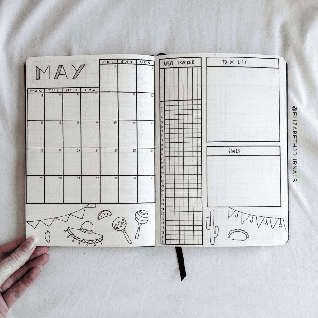notebook on white background open to may monthly log page. calendar, title, and cinco de mayo doodles on left page. right page includes doodles and trackers