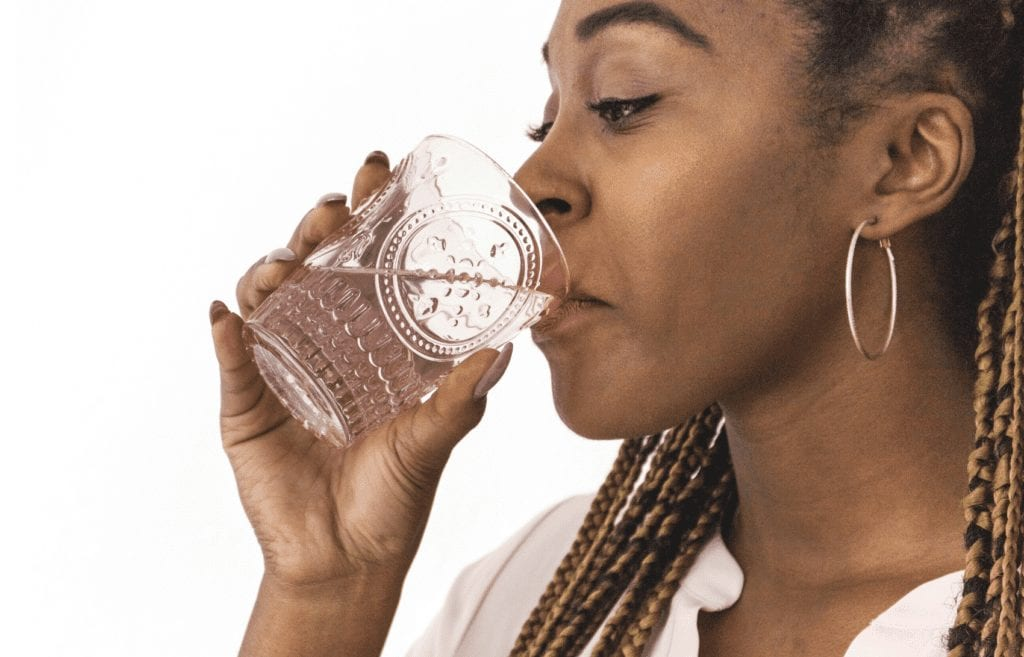 lady drinking water out of glass