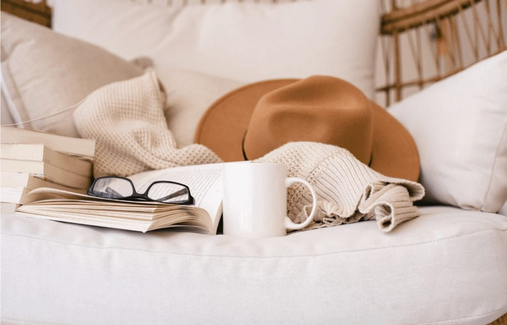 mug gllasses and books on neutral colored couch