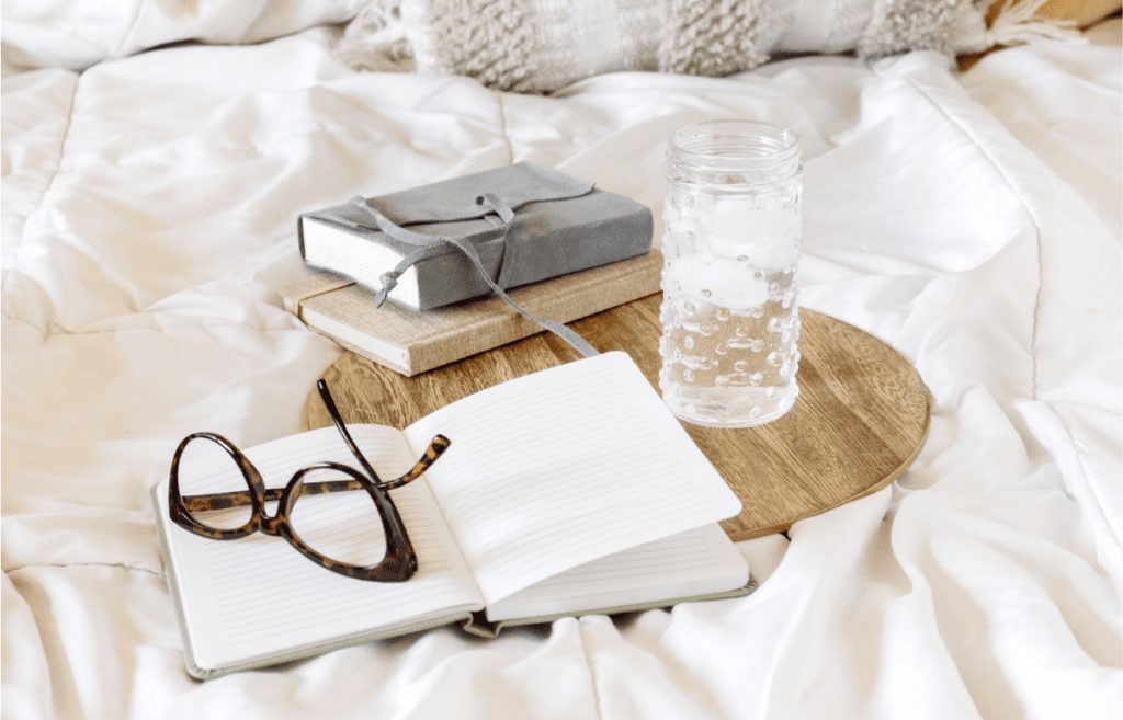 book glasses water, candle on white bed sheet