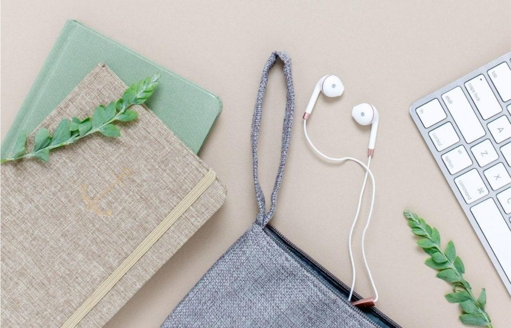 notebooks green and tan hand bag headphones and keyboard on tan background