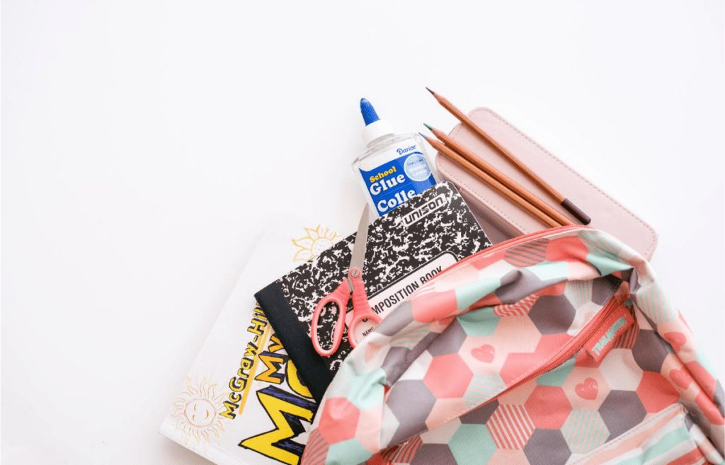 pink and gray backpack with school supplies poking out - notebook pencils glue