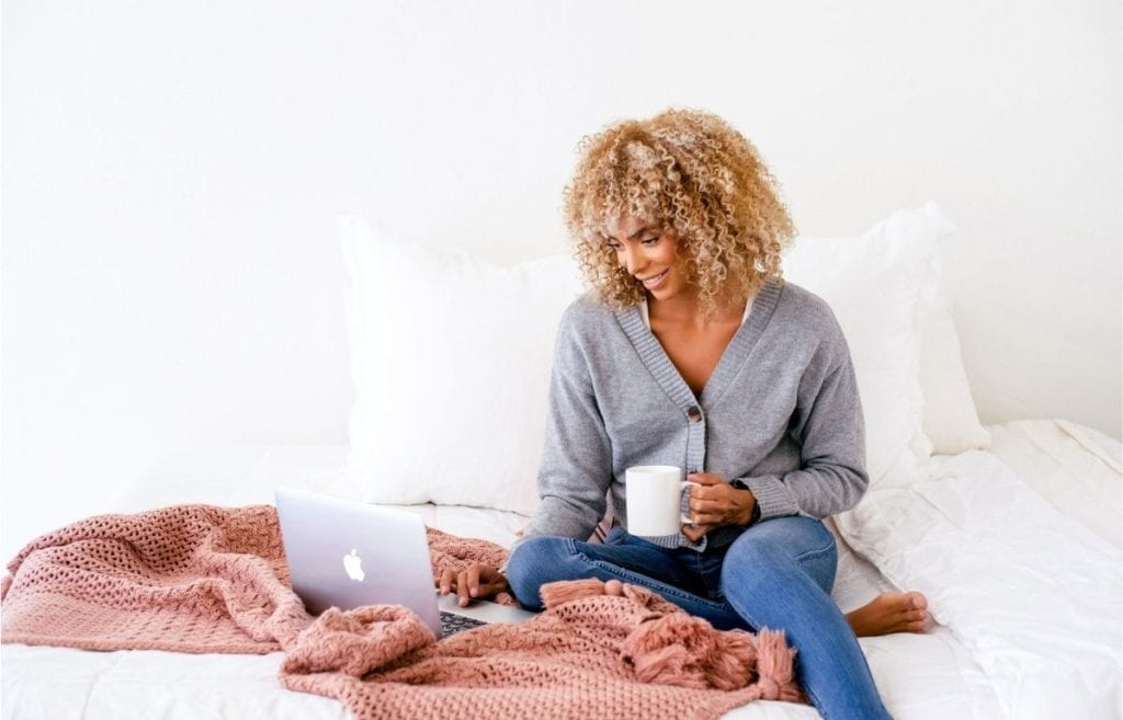 woman on bed with laptop and mug