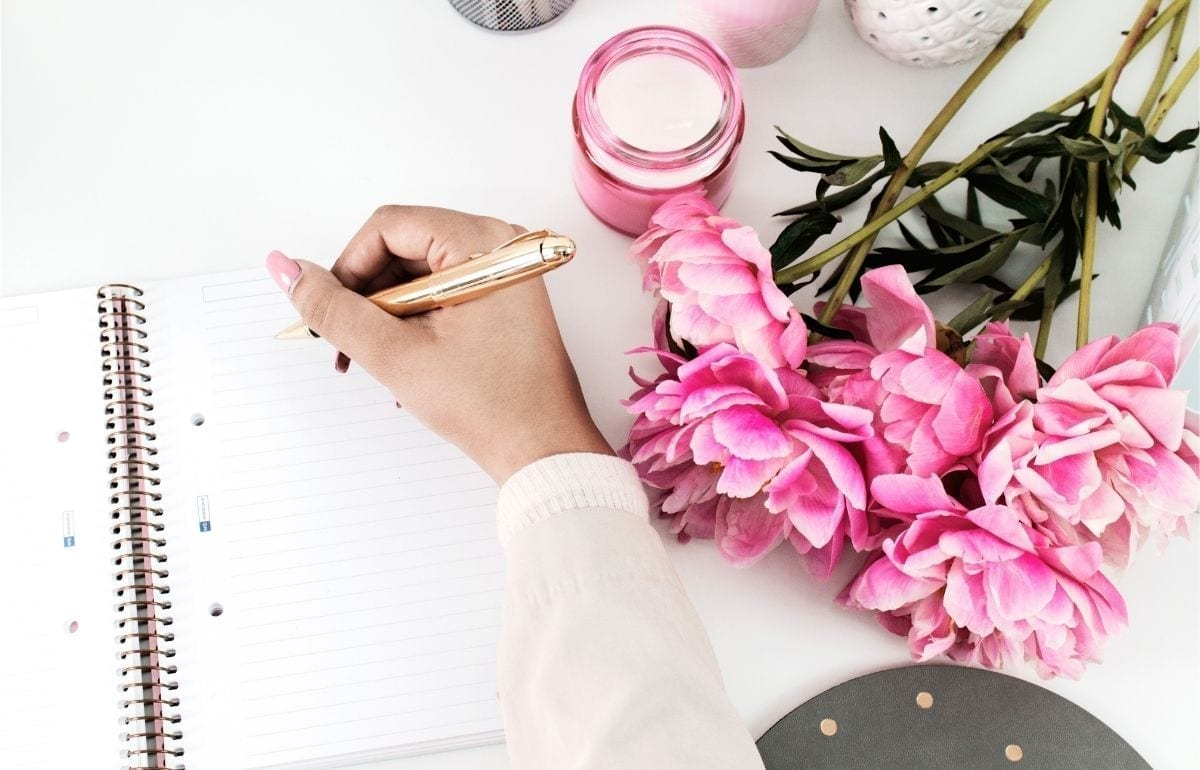 hand hold gold pen write in lined noteobook_pink flowers and candle nearby