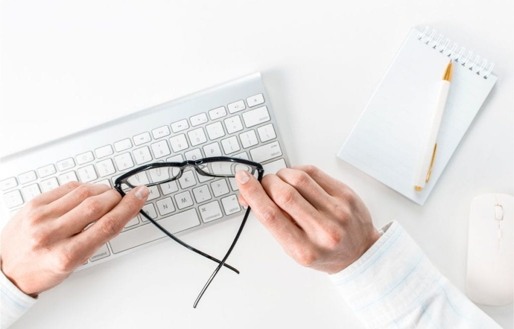 hands hold glasses over keyboard with notepad and pen