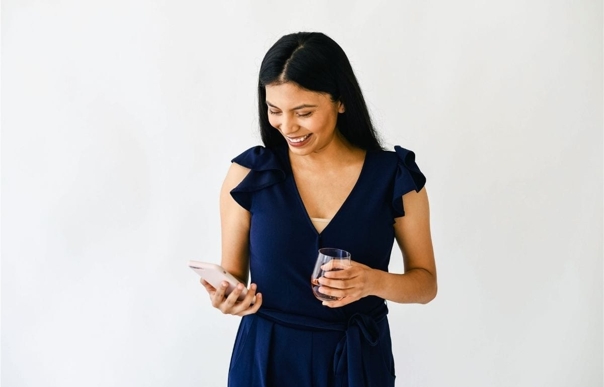 business woman smiling at phone holding wine in dark blue dress
