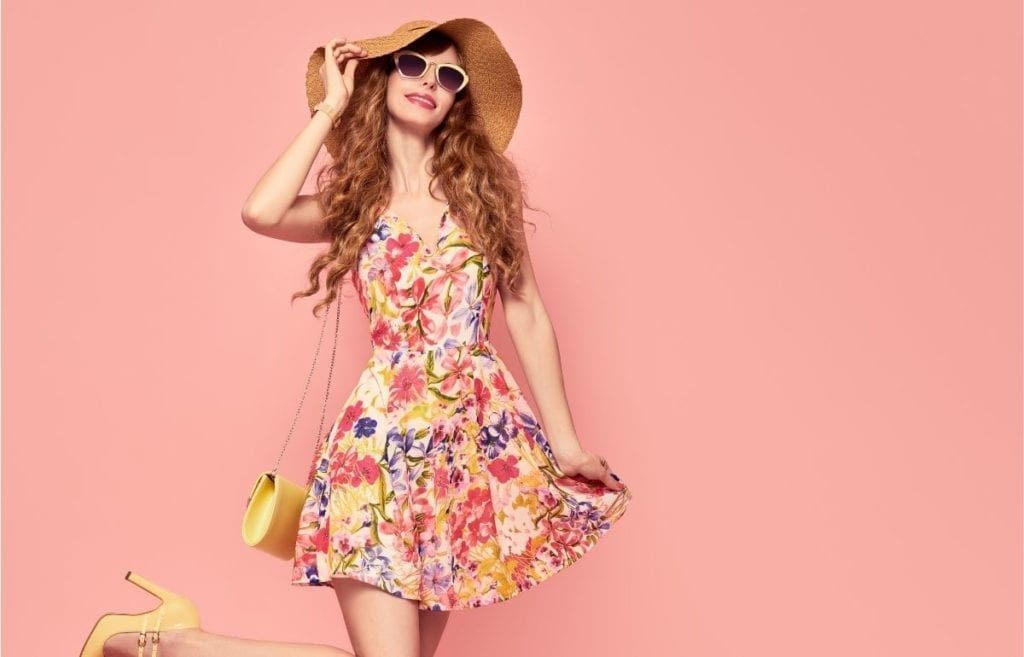 pink background red haired female sun hat and floral dress