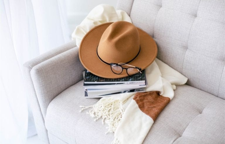 hand glasses books and scarf on couch
