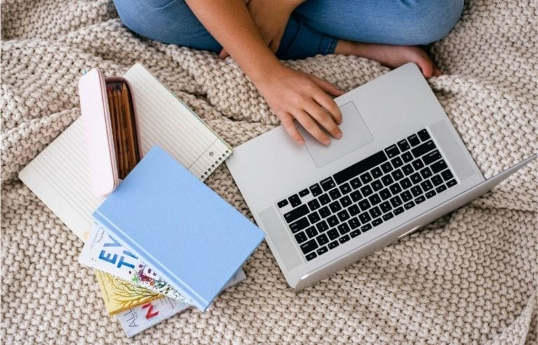 student with laptop, notebook, and books on tan colored blanket