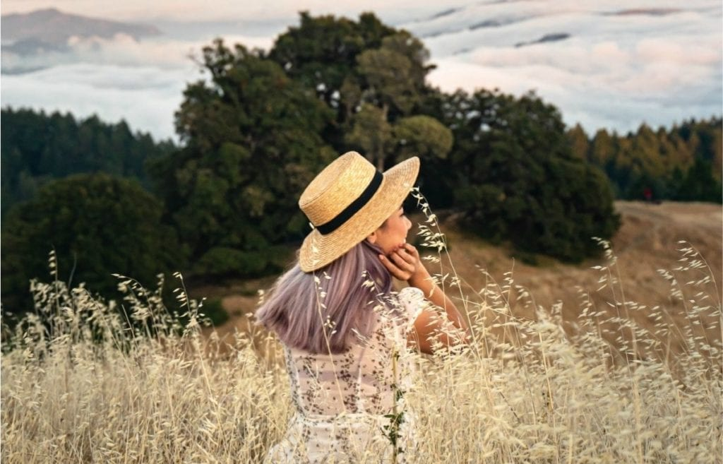 woman with sunhat in wheat field looking off into the distance