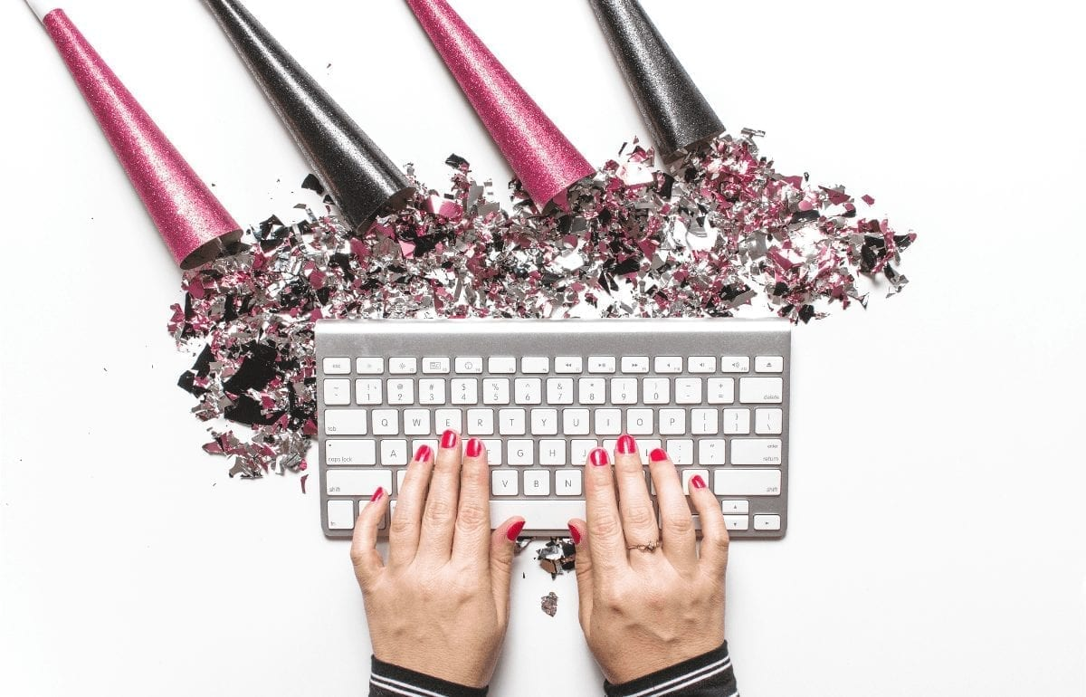 female hands on keyboard with pink streamers