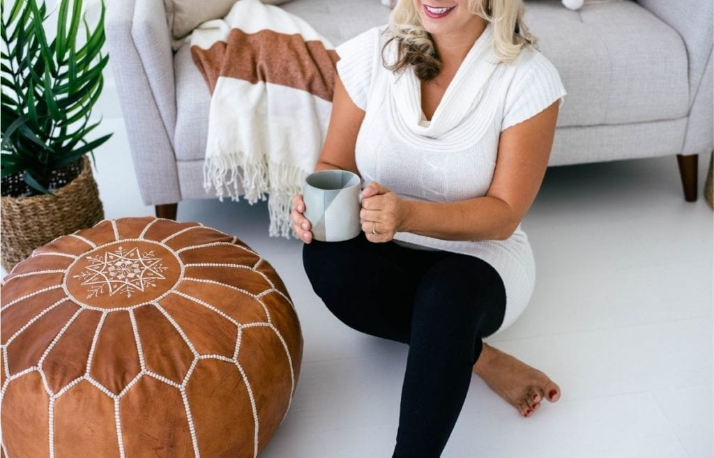 woman wearing white with coffee mug on floor in front of light gray couch and brown leather pouf