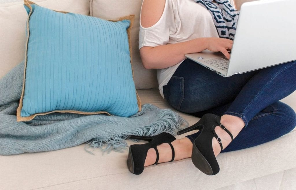 woman with laptop sitting on light gray couch with light blue pillow and blanket