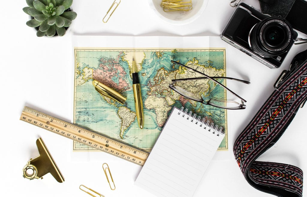 Flat lay including green map, glasses, gold pen, gold paperclips, small notepad, camera, succulent, wooden ruler