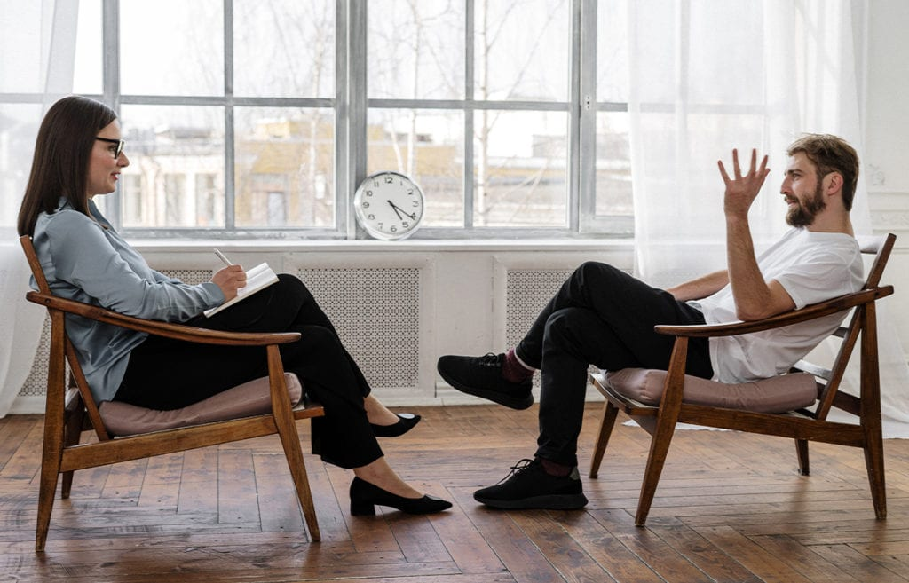 A man and a woman sitting on chairs facing eachother and talking