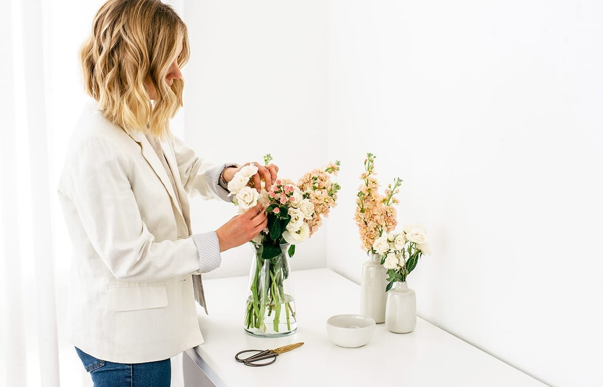 A woman standing at a table arranging a spring flower bouquet in a vase