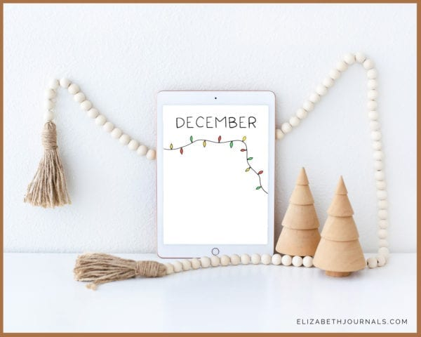 minimal habit tracker mockup-tablet propped against wall surrounded by wooden christmas trees and string of white wooden beads-background is white