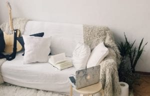 a white counch in a living room with neutral colored blanket drapped over edge, varied pillows, a guitar, open book, laptop on side table, and snake plant tucked behind
