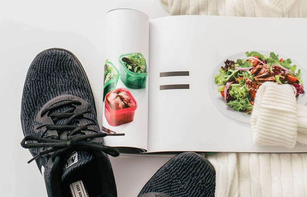 black running shoes, healthy eating magazine open to photo of brightly colored food over a white blanket