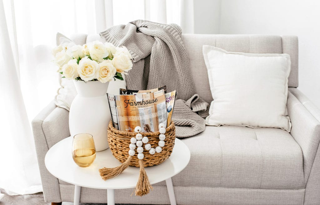 A vase of flowers on a table next to a basket with farmhouse magazine in from of light gray couch with neutral toned pillows and blankets