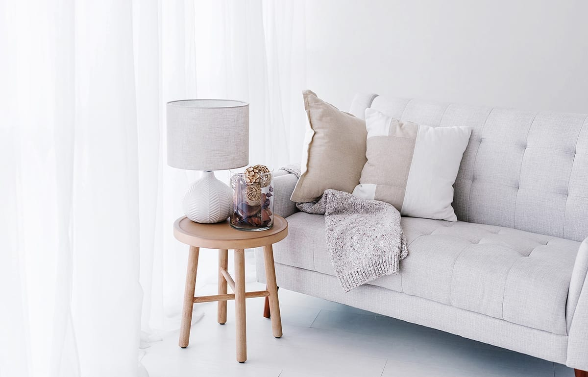 A gray sofa in a room with neutral toned pillows, wooden side table, and vase with pinecones in it