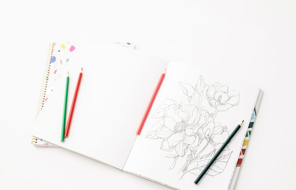 coloring book featured uncolored floral page and colored pencils