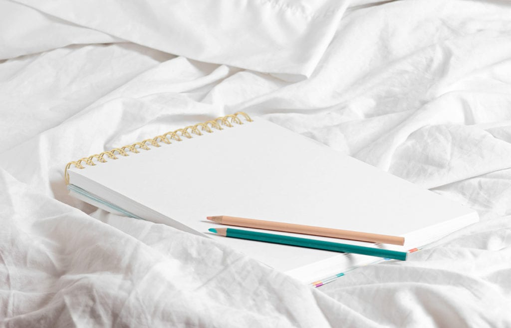 doodle notepad with colored pencils on white sheet