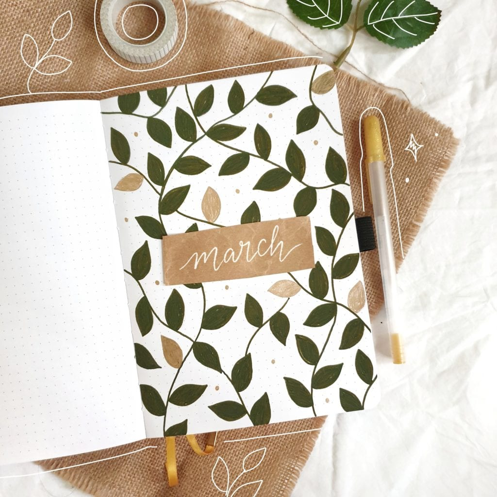 bullet journal on white and brown cloth. page has dark green vines and a few gold leaves