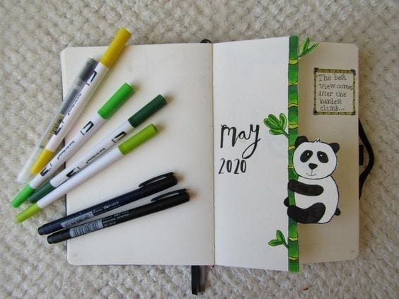 open notebook with green and yellow markers. open to may 2020 cover pae with panda climbing bamboo
