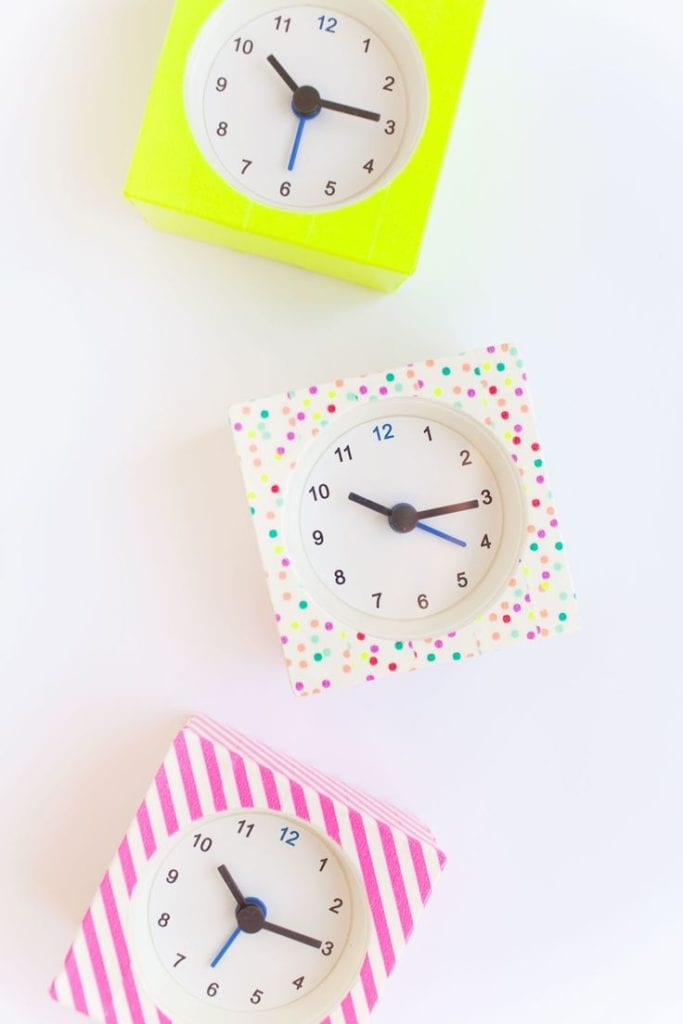A clock on a table decorated with dotted and striped washi tape