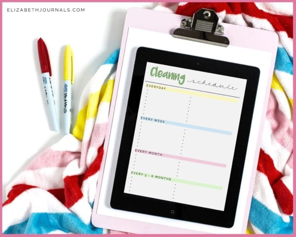 colorfully striped blanket with red and yellow markers and tablet on clipboard previewing cleaning schedule