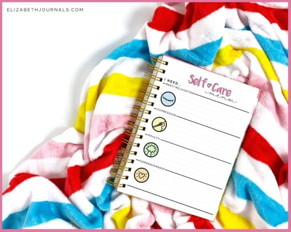 colorfully striped blanket with spiral bound notebook previewing self-care menu