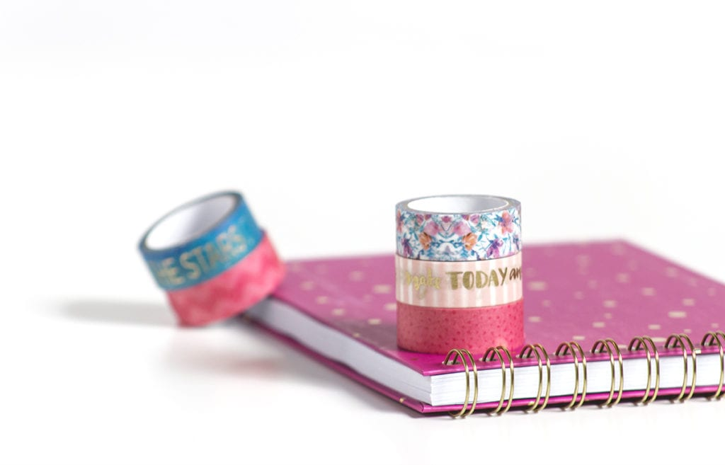 A cup of pink, blue, and floral washi tape and pink notebook on white surfaceon a table