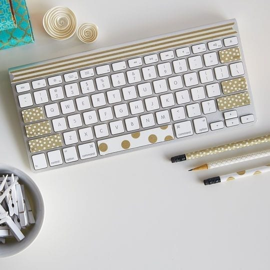 keyboard decorated with gold dotted and striped washi tape