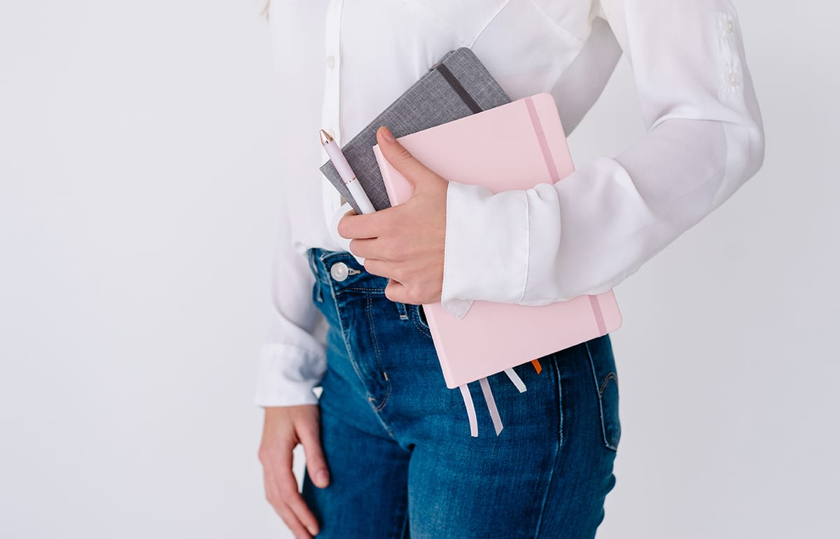Featured-Image-Care First Year Teachers-women holding notebooks dressed business casual close up on torso area