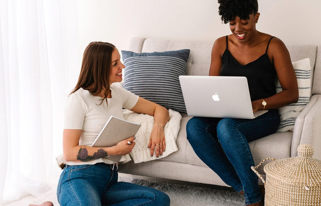 Featured-Image-time management distractions-women on couch with laptop smiling at women on floor with notebook