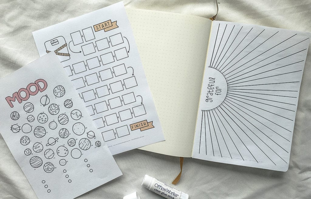 notebook open to page with printable pasted in and two loose printable pages laying on blank page