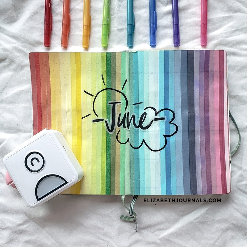 """rainbow background with """"june"""" in script font sun upper right and cloud bottom right. poooli printer on bottom left. rainbow ordered pens along the top"""