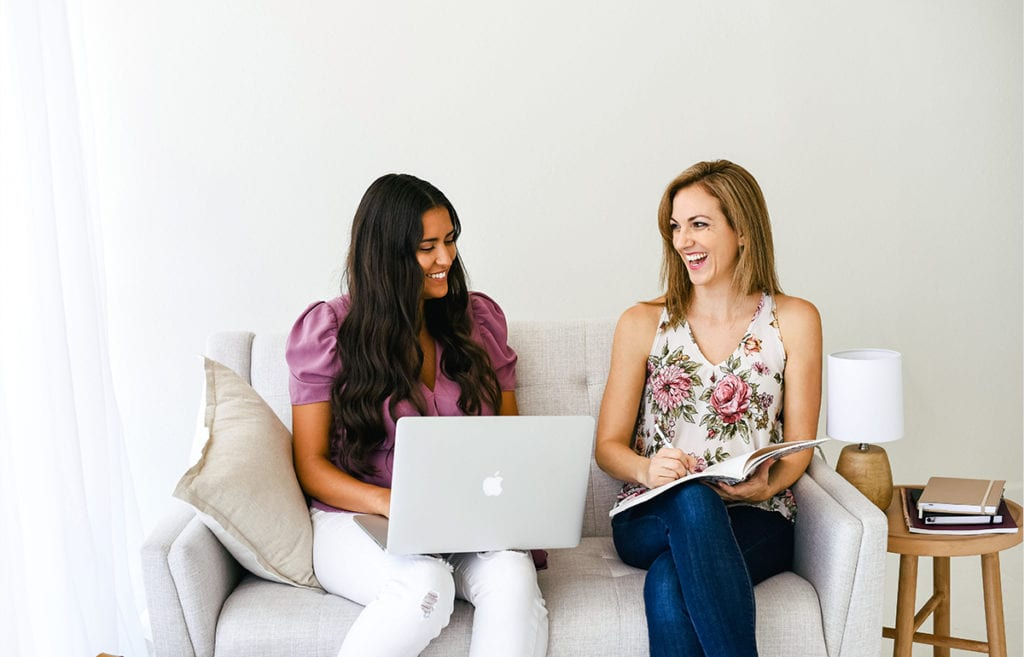 two women on couch smiling-one with laptop-one with notebook