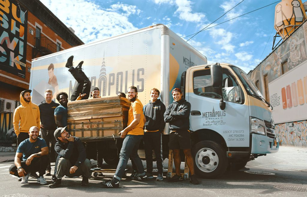 organize your move - group of friends carrying boxes standing in front of moving vehicle