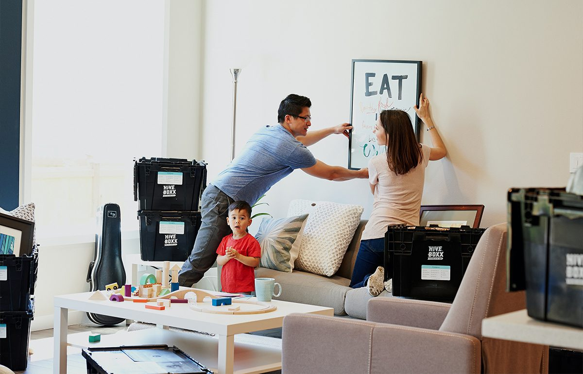 Featured-Image-organize your move - man and women taking down photo to move while child plays with toys on table