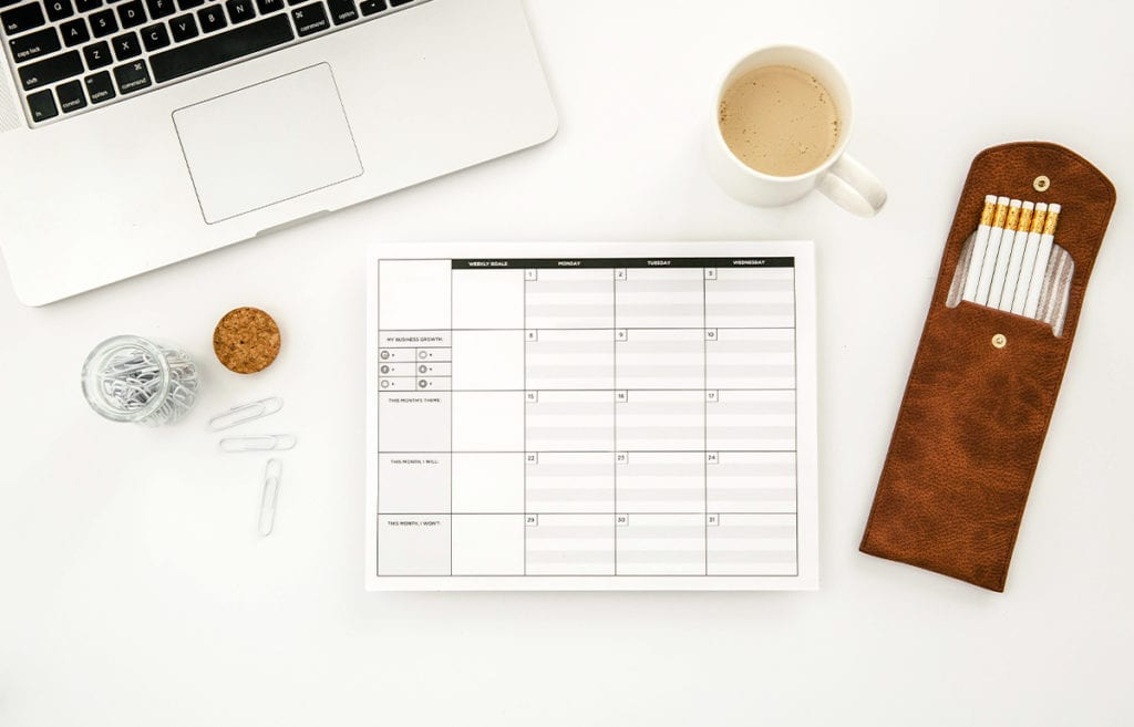 featured image-5 ways to use a calendar to improve productivity-calendar on white surface with white stationery coffee and calendar