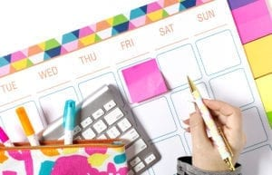featured image-5 ways to use a calendar to improve productivity-person writing on brightly colored calendar