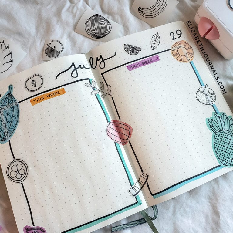 """image of open notebook to weekly log week 28 and 29 header in script """"July"""" and fruit doodles scattered through the rest of the page. image tilted left"""