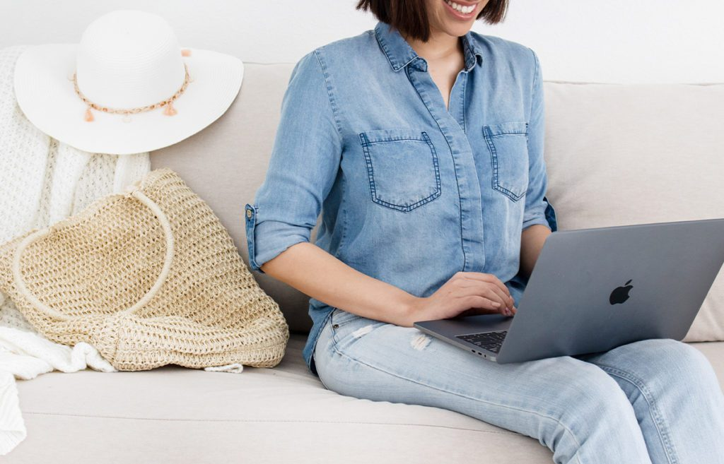 women sitting on floor leaning on couch with laptop in lap