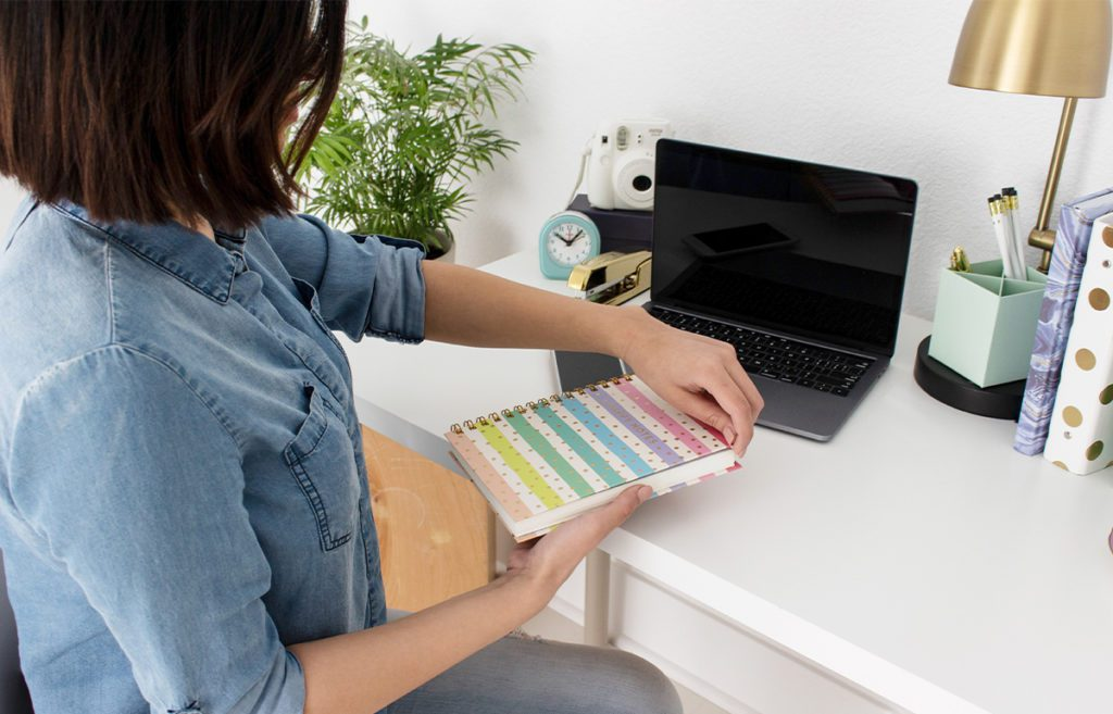 women sitting at desk with planner and laptop