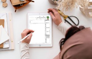 woman at desk using tablet to use digital calendar. Desk covered in decor and stationery